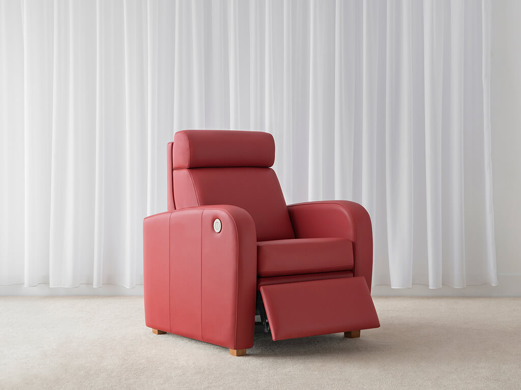 retro recliner chair upholstered in red leather with wide arm rests and high back