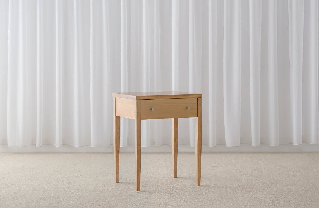 contemporary timber bedside table on tapered leg with single drawer