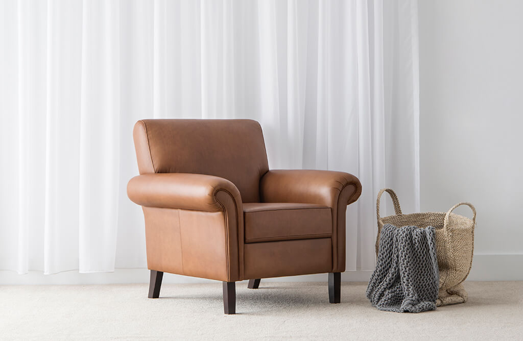 tan leather armchair with rolled arm and high back for comfort finished with timber legs