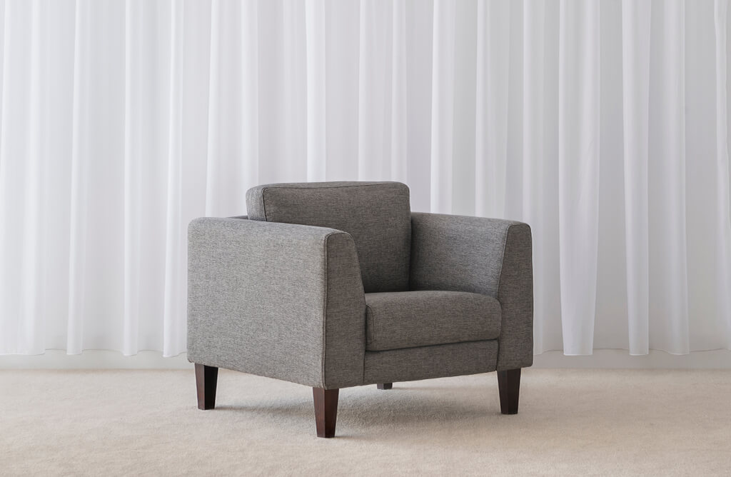 comfortable fabric arm chair in grey blue colour with low back and wide seat and arms sitting on dark timber legs