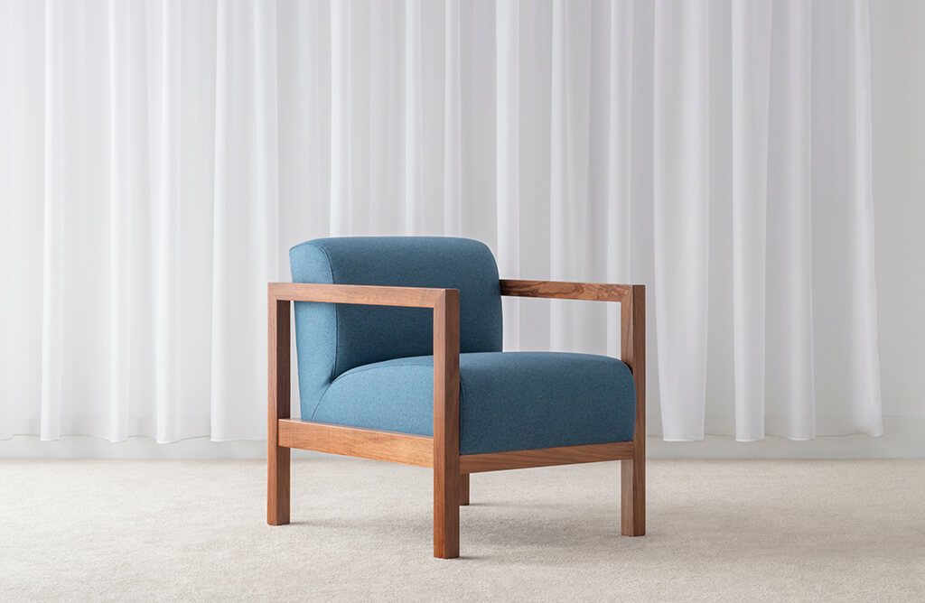 blue fabric arm chair with square timber arms and rounded cushions