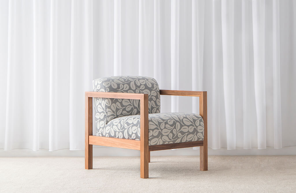 Scandinavian arm chair with square timber arms and rounded seat and back cushions upholstered in floral fabric