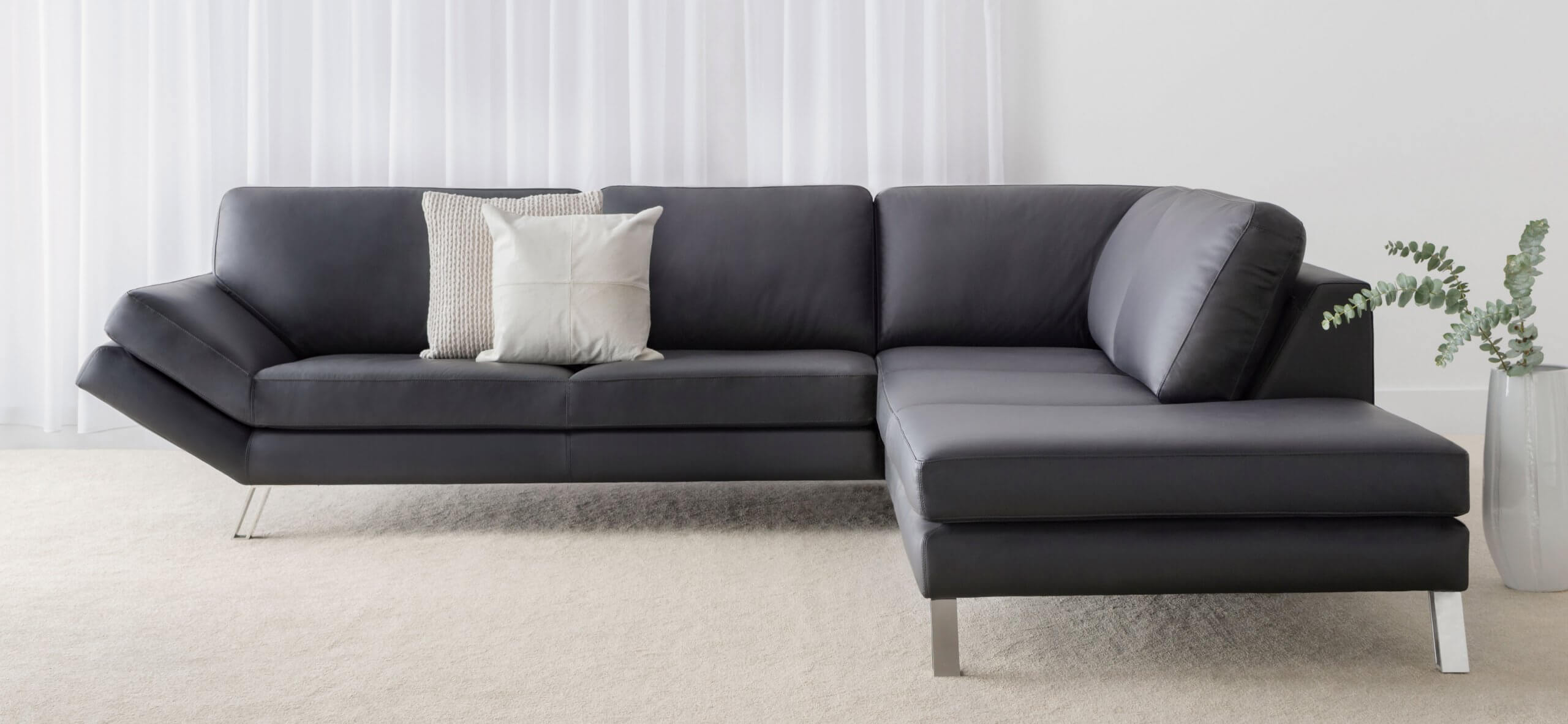 modern leather modular sofa with chrome legs and angled arm feature