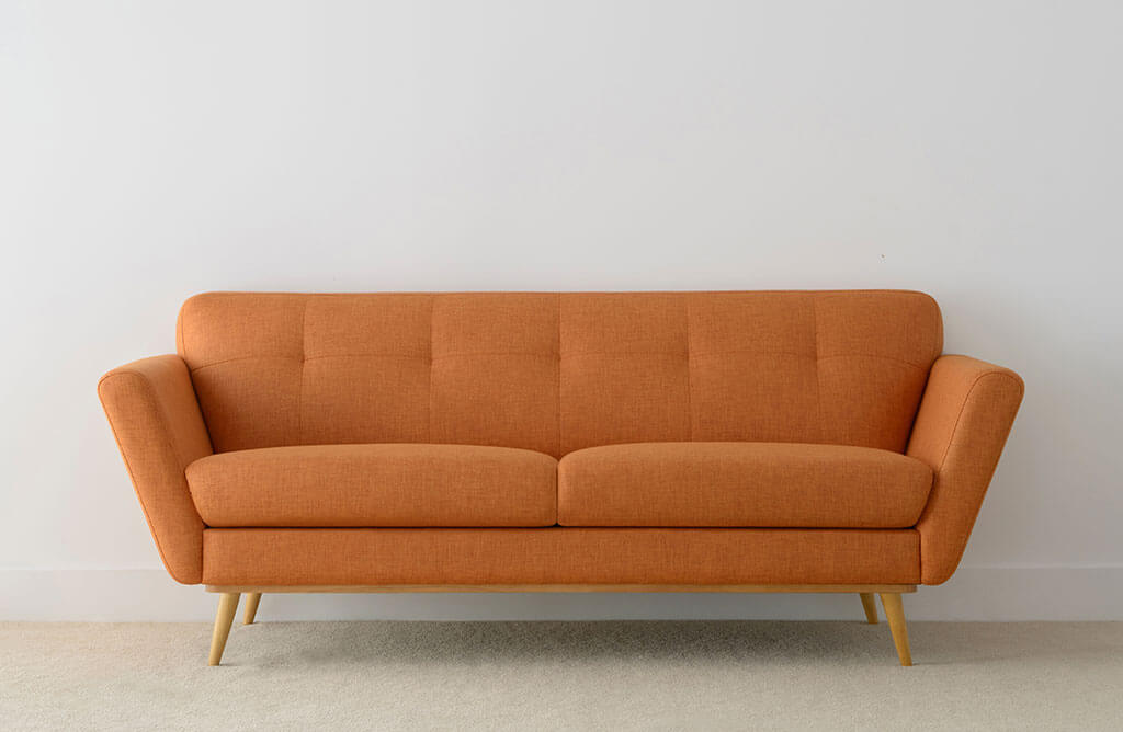 modern 3 seater lounge upholstered in bright orange fabric with pleated details and rounded timber legs
