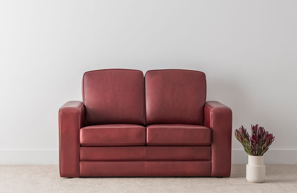 traditional leather lounge in burgundy colour with firm arm rests and high back cushions