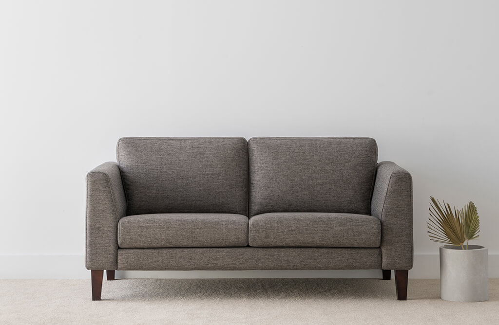 grey textured fabric sofa with firm angular arm rests and low back feature