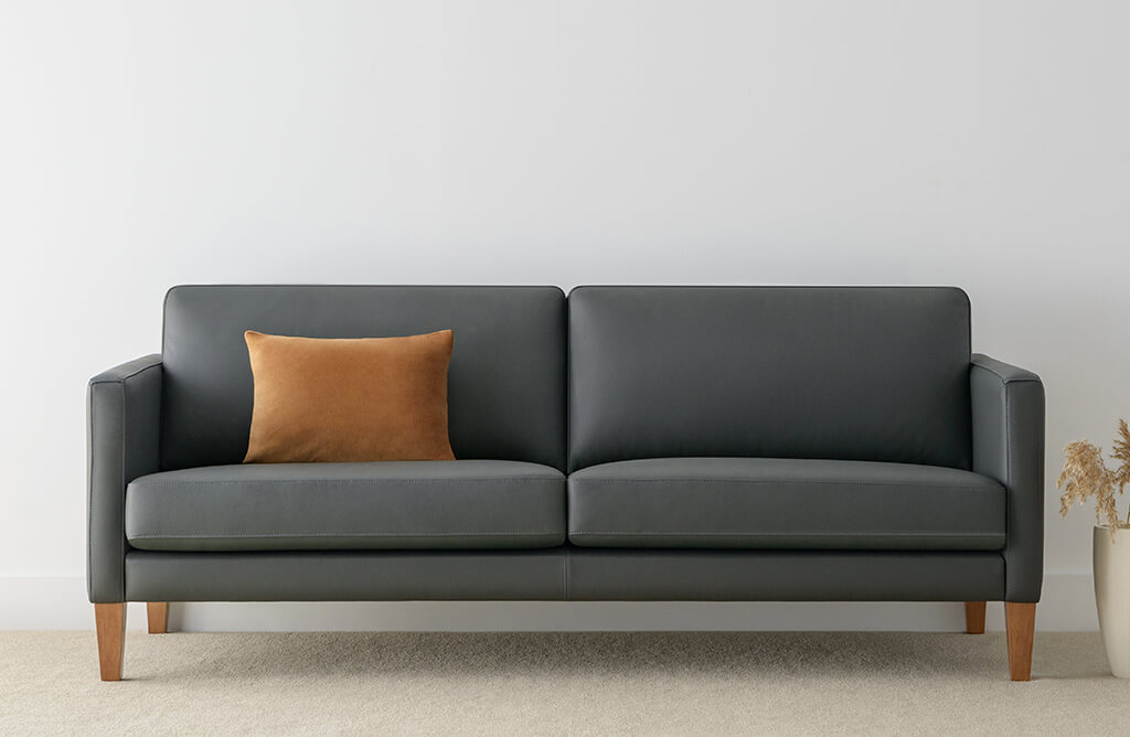 soft black leather lounge with slim lines and timber legs