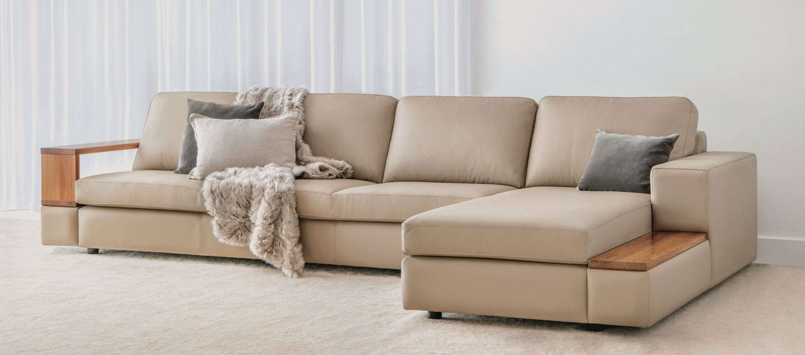 modular sofa upholstered in leather with wide cushions and timber arm features