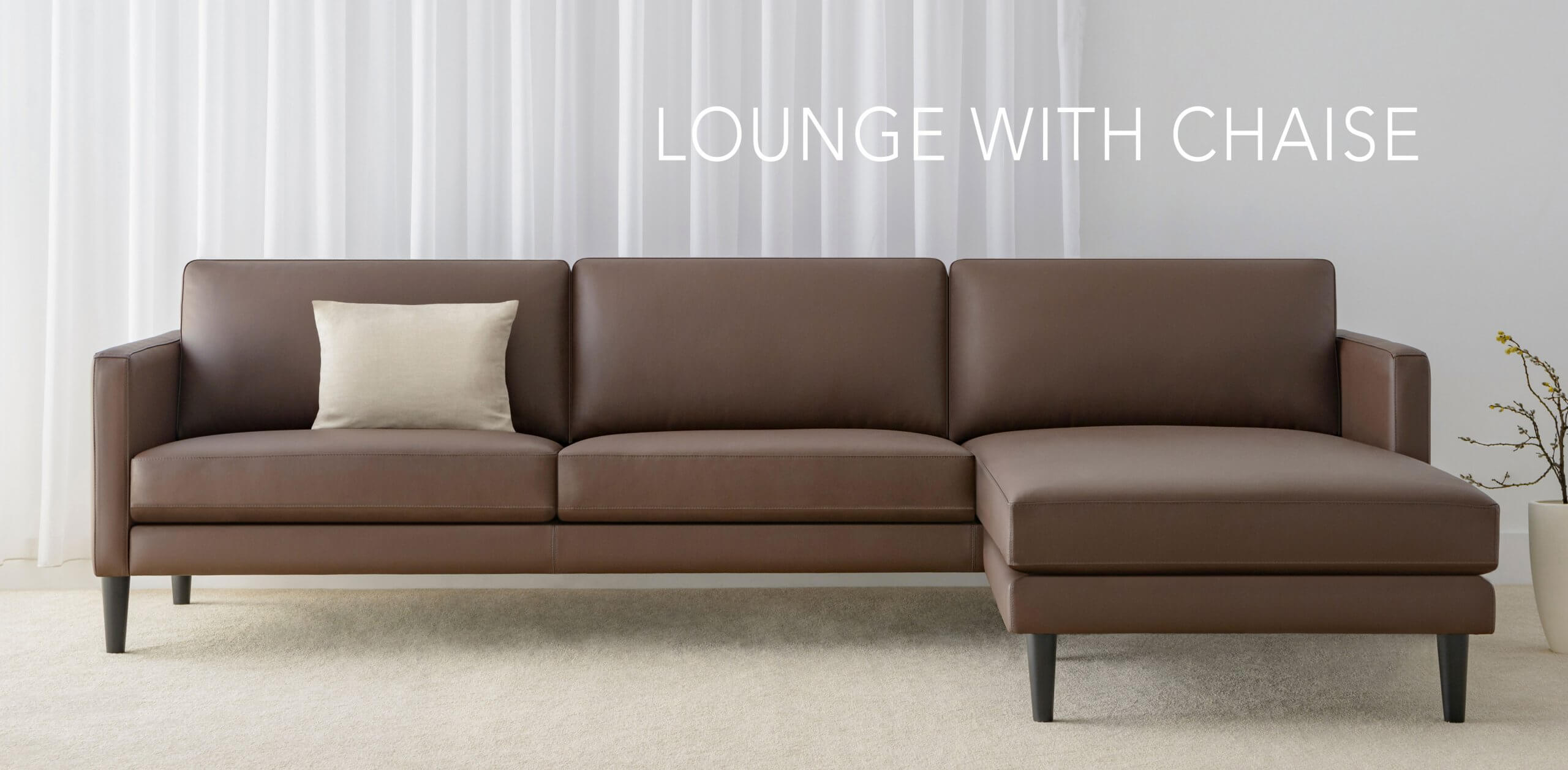 4 seater leather lounge with chaise and low back cushions on rounded timber legs