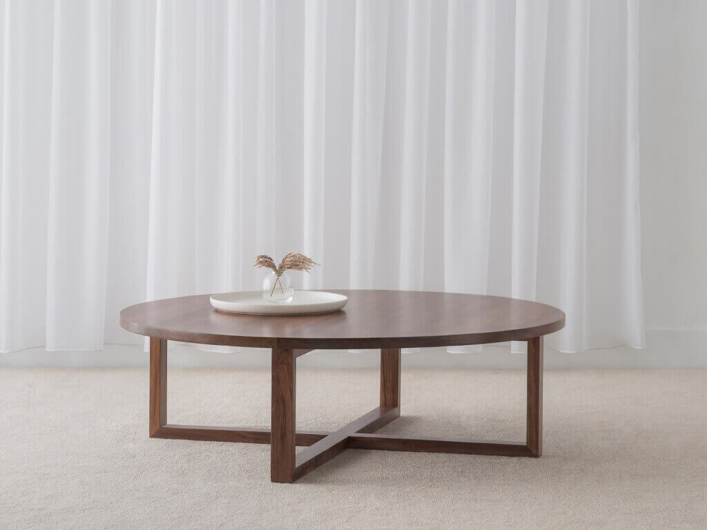 designer circle coffee table with wide open cross legs made in solid blackwood timber
