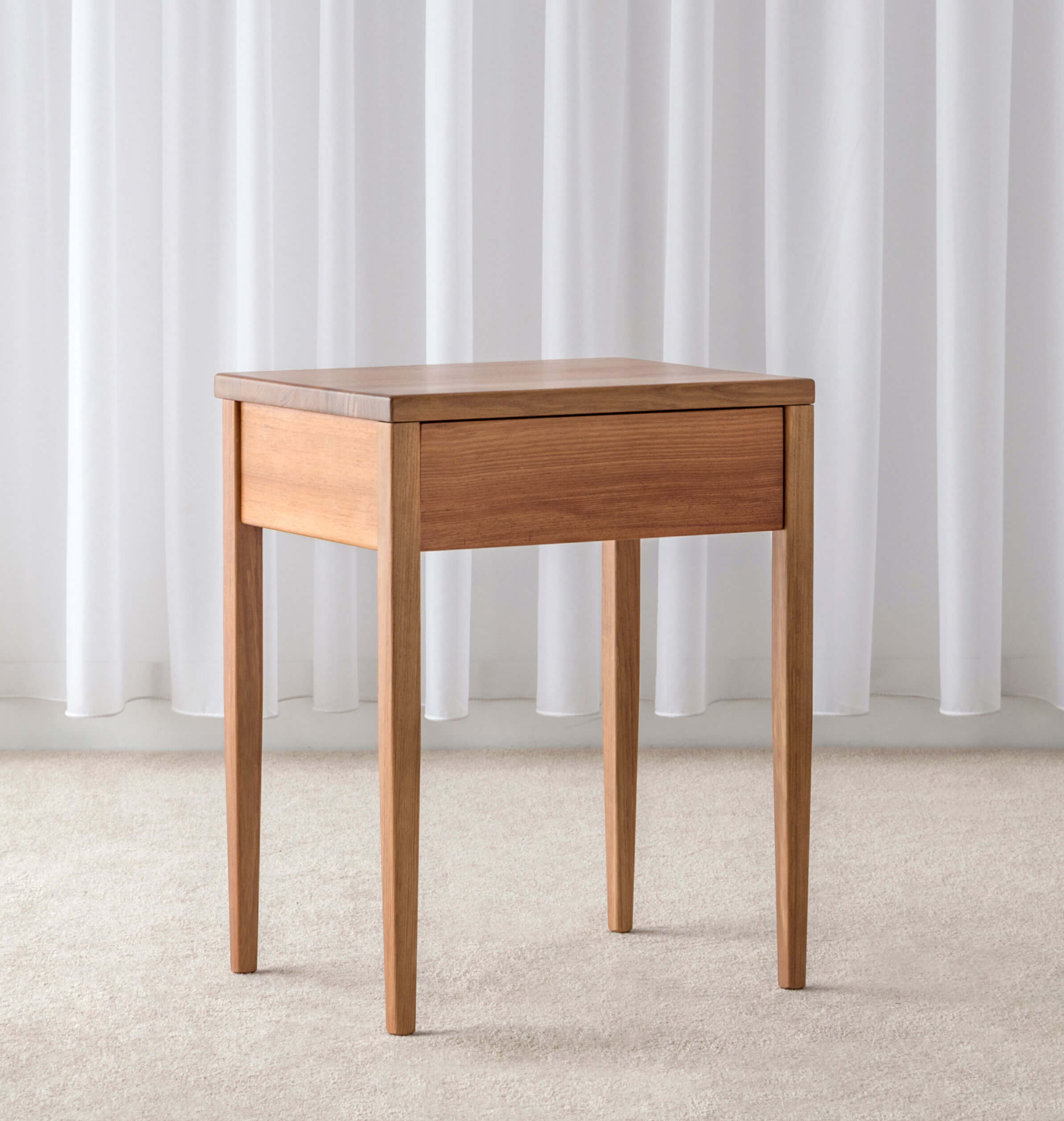 wooden bedside table with tapered legs and finger pull drawer