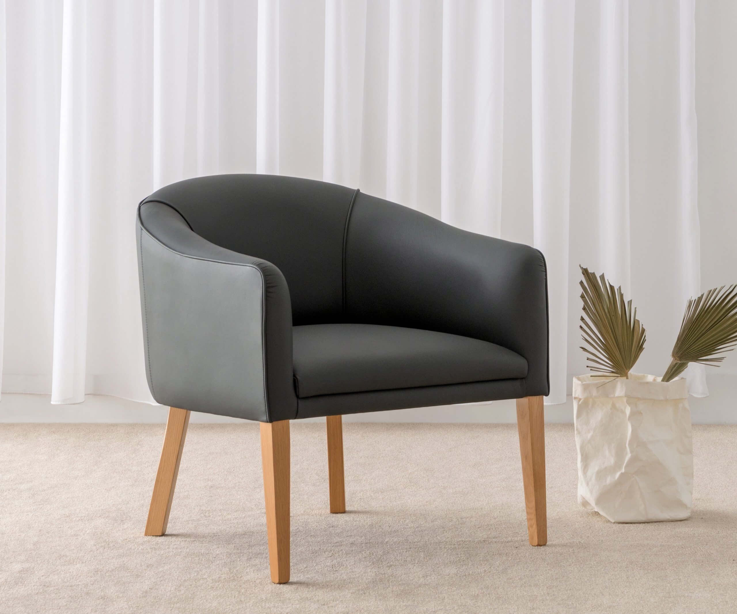 Leather tub chair with timber legs
