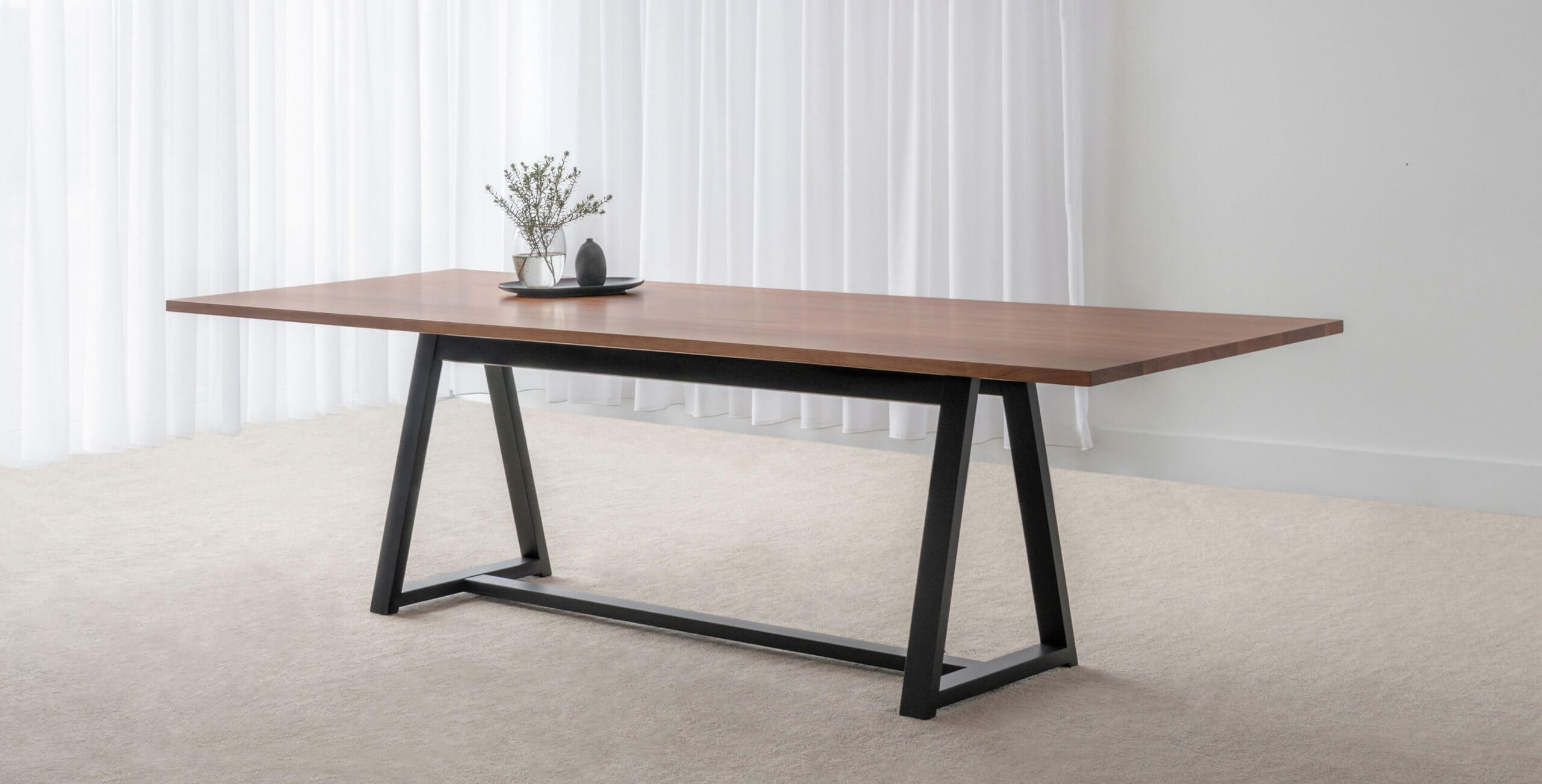 modern timber dining table with tapered top and black base